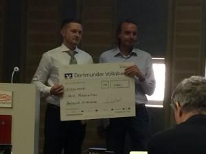 Dr. Sebastian Wenzel, Vorstandsmitglied des FVI, überreicht Bert Möschwitzer den Scheck über 1.000 Euro.